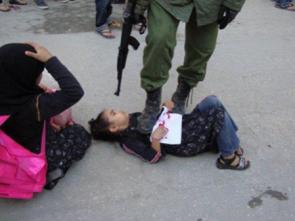 soldat israélien pointant son arme sur une jeune fille à terre